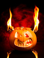 Evil Halloween pumpkin with flames and red smoke.
