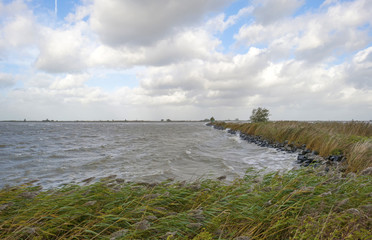 Storm over a lake along a dike at fall