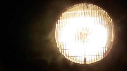 Headlight blinks in a fog.