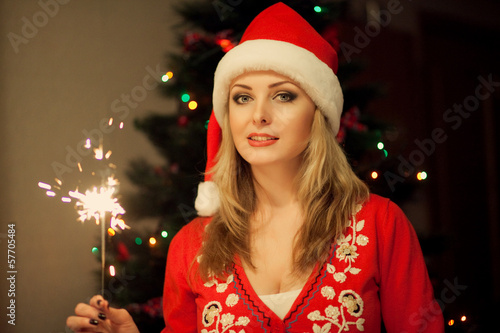 Woman with the sparkler and santa's hat in the night of new year