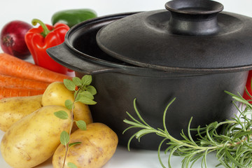 Fresh vegetables and herbs with iron pot closeup