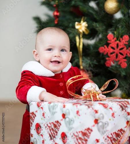 kid girl dressed as Santa Claus at Christmas tree with