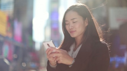 Asian woman in New York City texting message