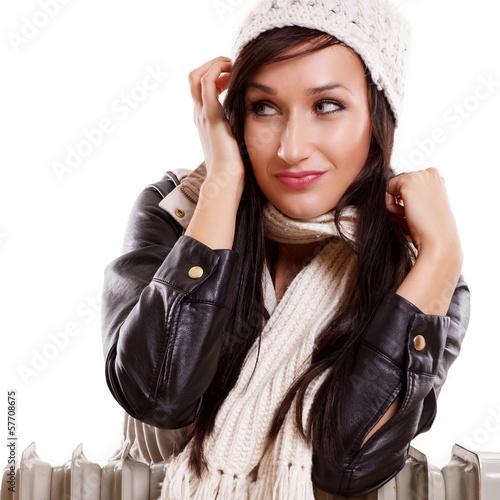Frau im Winterkleidung stützt sich auf Heizkörper