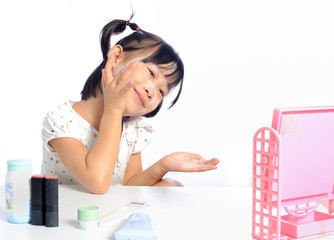smiling asian little girl is applying make up baby powder her fa