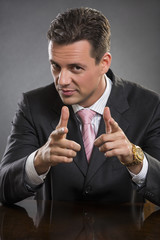 Successful handsome businessman pointing at you