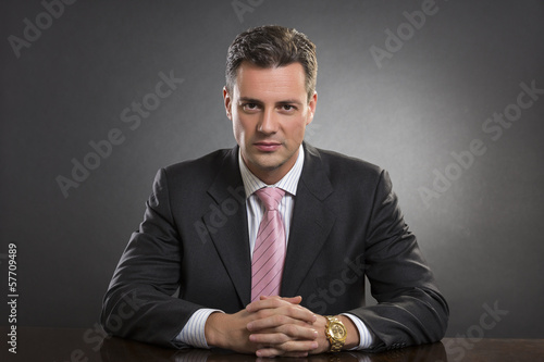 Successful confident manager in black suit over dark background