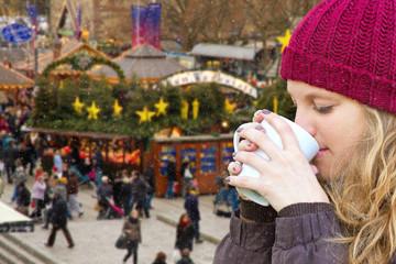 Junge Frau beim Glühwein trinken auf dem Weihnachtsmarkt