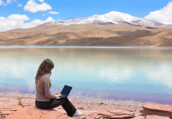 Woman with laptop on the shore lake Laguna Celeste