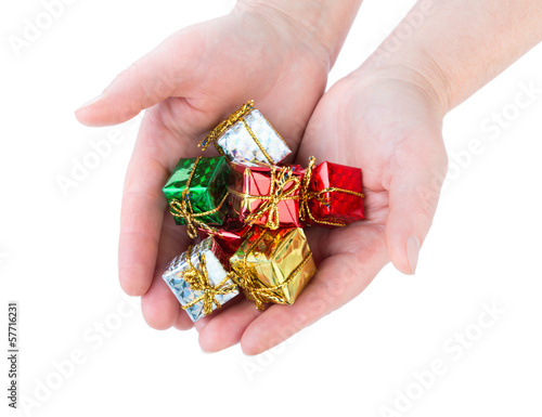 Woman holds many beautiful little Christmas gifts on white backg