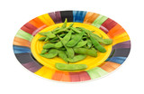 A serving of edamame pods on a colorful plate