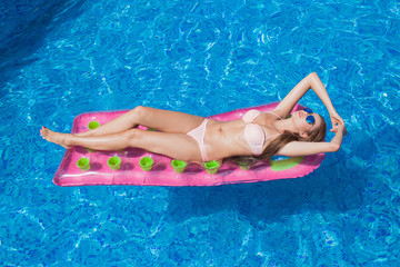 beautiful girl floating on a mattress in the sea or swimming poo
