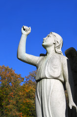 Angel statue in cemetary with raised arm