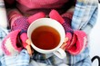 Cup of hot tea in child girl's hands