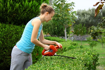 woman pruning shrub with tool in garden