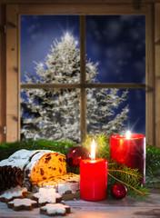 Christstollen bei Kerzenlicht am Fenster