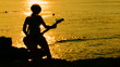Playing guitar on the beach at sunset
