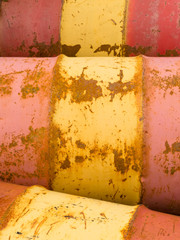 Rusty oil barrels yellow red background pattern