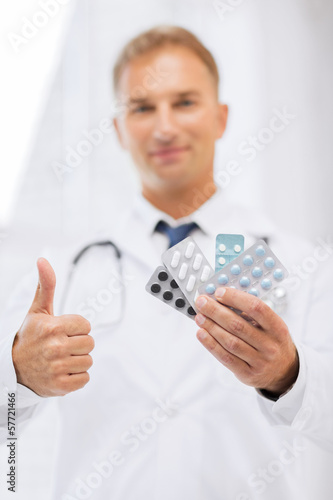 male doctor with packs of pills