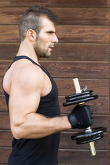 Portrait of sporty man exercising dumbbells.