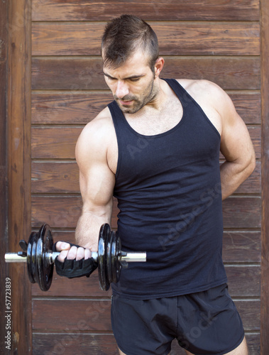 Muscular man exercising with dumbbell on wooden background.