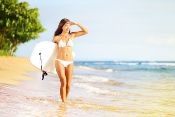Surfboard woman walking in beach water