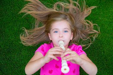 Blond kid children girl playing flute lying on grass