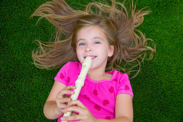 Blond kid children girl playing flute lying on grass