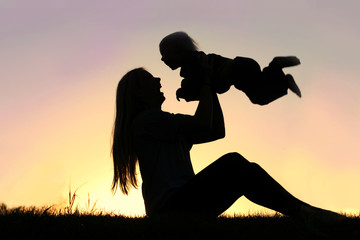 Silhouette of Laughing Mother and Baby Playing Outside