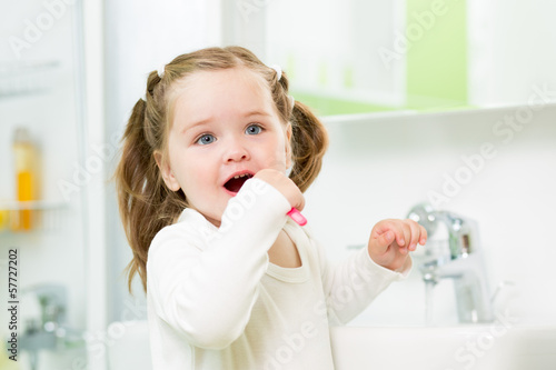 Child girl brushing teeth in bathroom