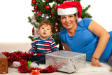 Cheerful mom and son under Xmas tree