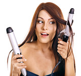 Fototapety Woman holding iron curling hair.