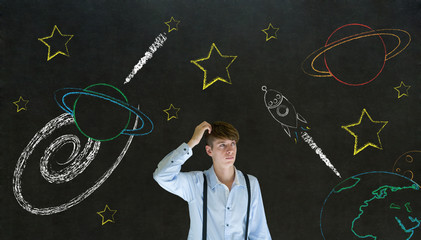 Businessman scratching head with solar system on blackboard