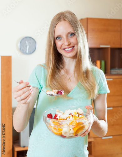 Happy blonde woman eating  fruit salad