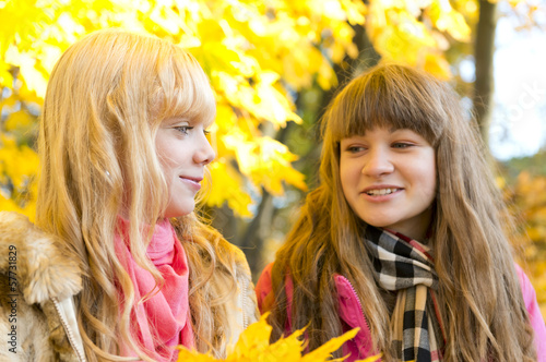 Two beautiful girls talk in autumn park