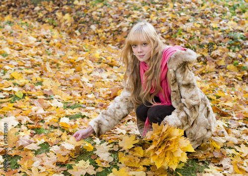 Beautiful girl with blond hair collects autumn leaves  in park
