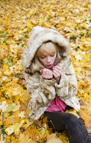 Beautiful girl warms the frozen hands in autumn park