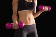 Slender active woman lifting pink dumbbells