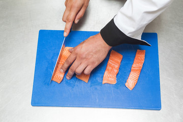 Chef slicing raw salmon with sharp knife