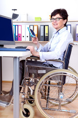 Sitting in a wheelchair working at desk