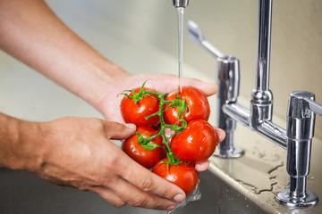 Kitchen porter washing tomatoes under running tap