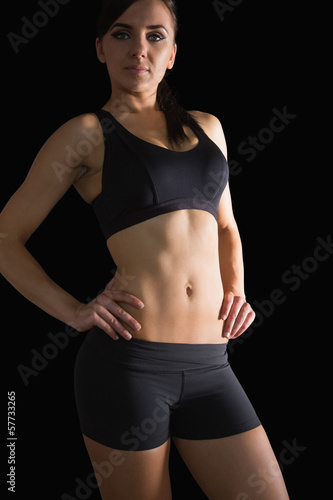Sporty slender woman posing in sportswear with hands on hips