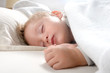 little blond boy sleeping on his bed relaxed
