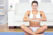 Cheerful young woman sitting in lotus position on a blue exercis