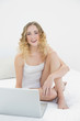 Pretty cheerful blonde sitting on bed using laptop