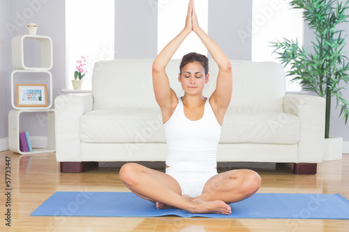 Slim brunette woman relaxing sitting in lotus position on exerci