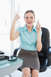 Classy happy businesswoman on the phone cheering with raised arm