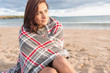 Beautiful  woman covered with blanket at beach