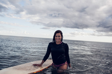 Portrait of a beautiful woman with surfboard in water
