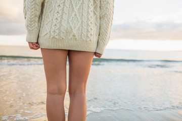 Mid section of a woman in sweater standing on beach